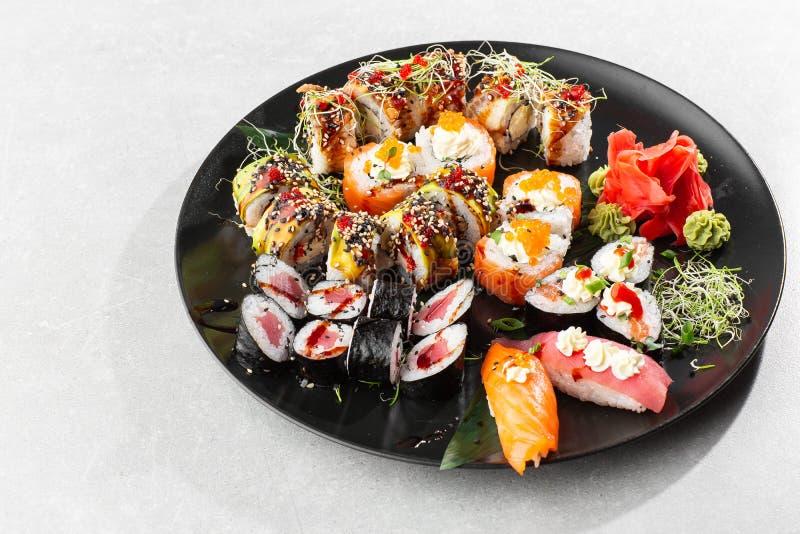 Japanese sushi set. Set of fresh tuna maki , salmon nigiri and dragon sushi rolls served on black plate close-up. Horizontal top. Japanese sushi set. Set of stock image