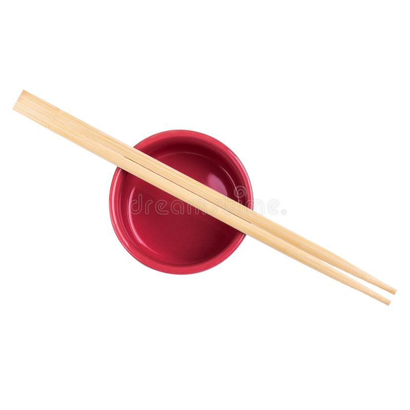 Japanese sushi sticks or chopsticks over red sauce bowl isolated on white background. Top view royalty free stock image
