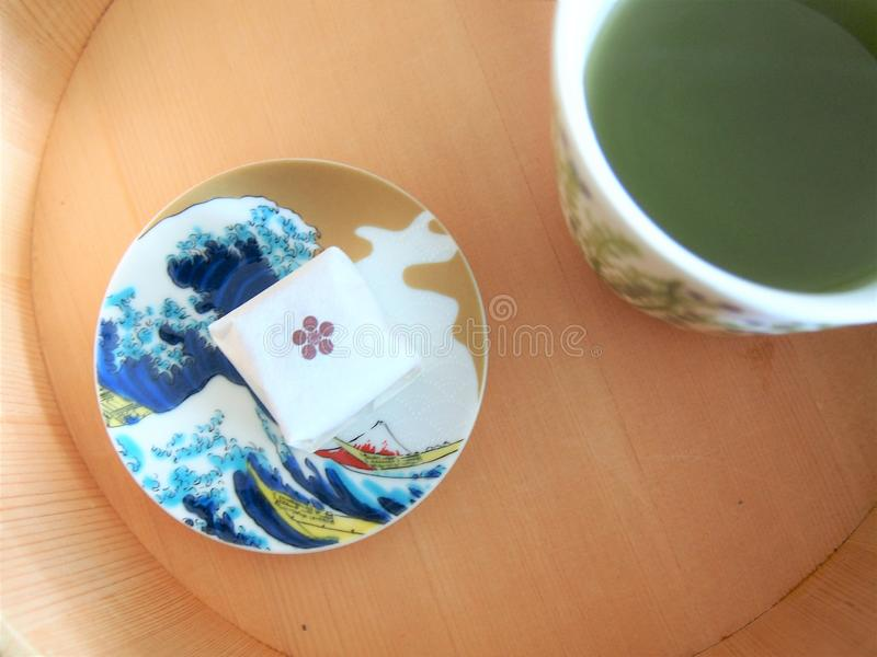 Japanese sweet, wooden sushi container and green tea stock image