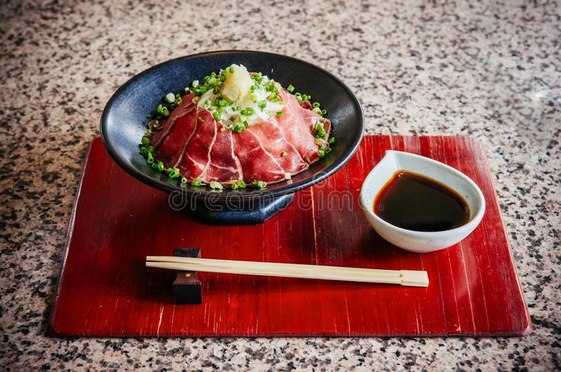 Japanese Tataki raw beef cuisine with ginger, onion, spring onion and soy sauce set on red wooden tray. Beautiful Japanese Tataki raw beef cuisine with ginger royalty free stock images