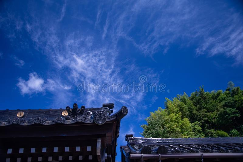 Japanese temple roof architecture agains a blue sky. Japanese temple tiled roof against a dark blue sky with a cloud scape. Japan architecture stock photography