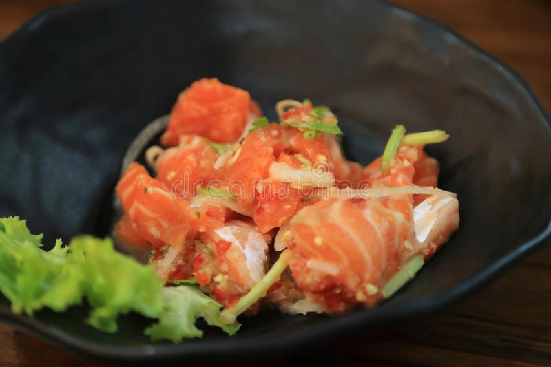 Japanese - Thai fusion food. Hot and sour Salmon sashimi. Thai style spicy salmon salad with mixed vegetables and herbs stock image