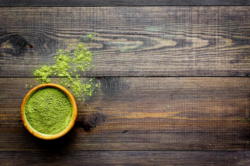 Japanese traditional product. Matcha green tea in bowl and scattered on dark wooden background top view copy space royalty free stock image