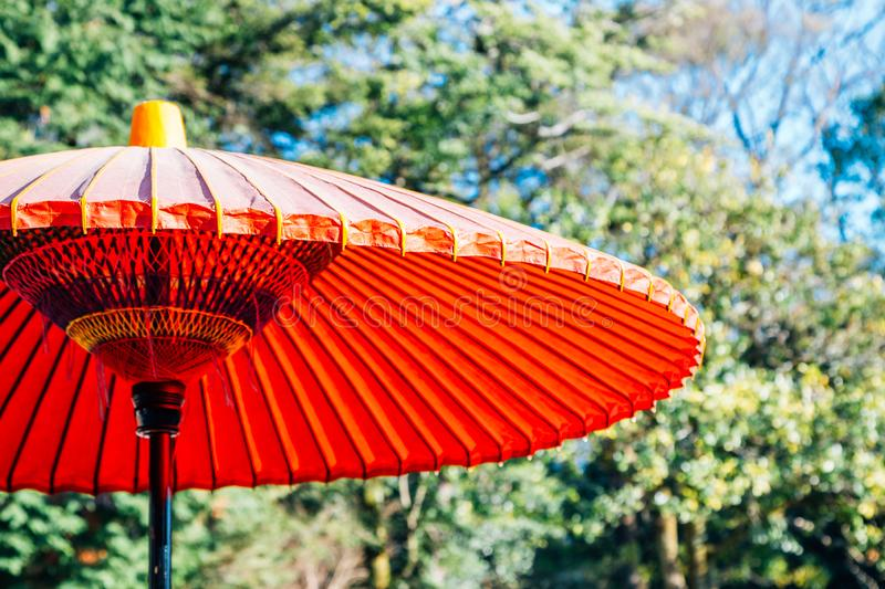 Japanese traditional red umbrella or parasol with green trees stock photos