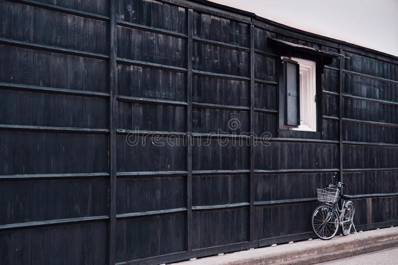 Japanese vintage white bicycle with black wooden wall of old house. Hida Furukawa, Gifu - Japan stock image