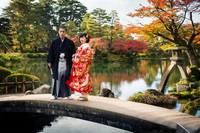 Japanese wedding couple in traditional kimono stand on a bridge in Kenrokuen park, Kanazawa city, Japan royalty free stock image
