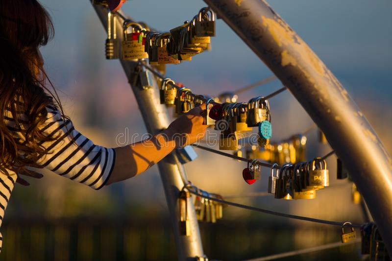 A Japanese woman adds her `love lock` to the growing collection in Kobe. stock photography