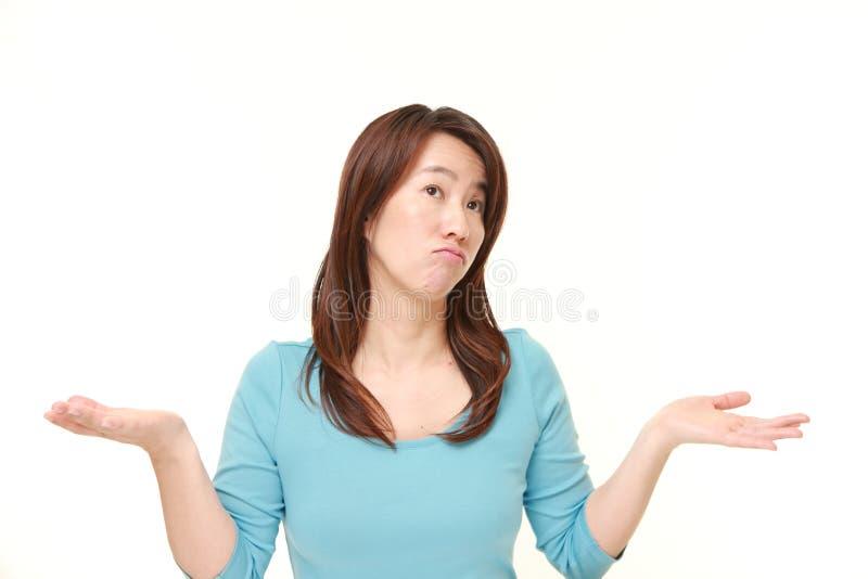 Japanese woman confused. Studio shot of Japanese woman on white background stock photo