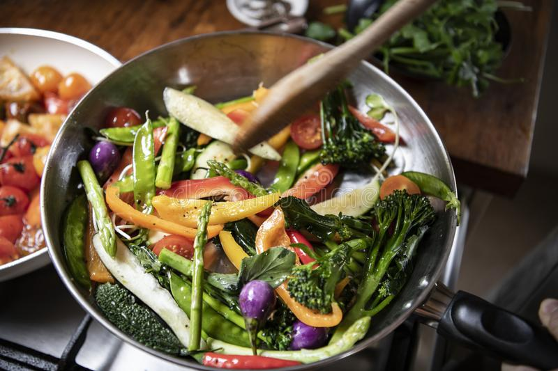 Japanese woman cooking stir fried vegetables stock image