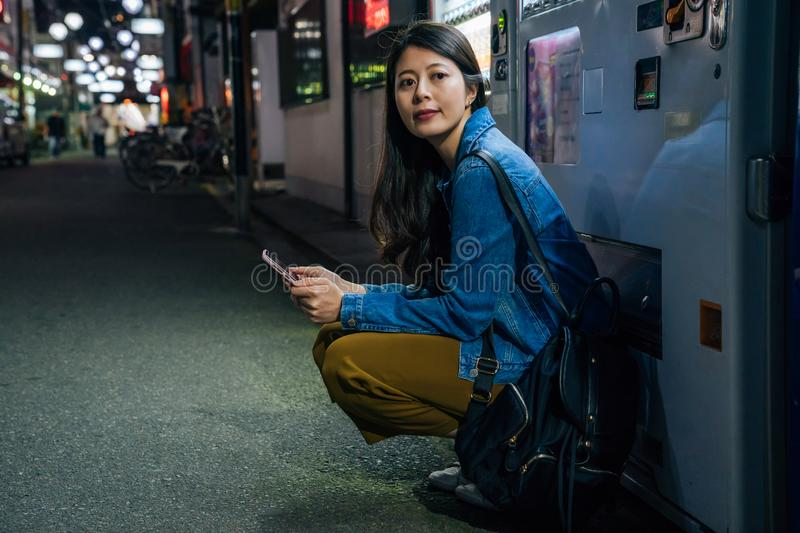 Japanese woman crouch down by the vending machine waiting for friend. elegant lady using cellphone contact app outdoor at night in royalty free stock images