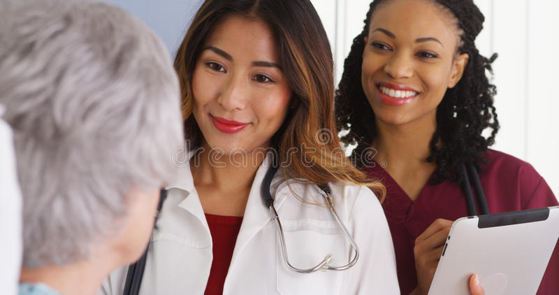 Japanese woman doctor and nurse talking to elderly patient in bed stock image