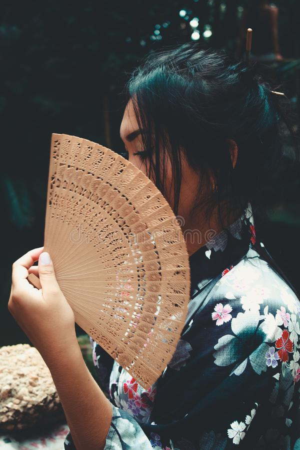 Japanese Woman Holding Brown Hand Fan royalty free stock photography