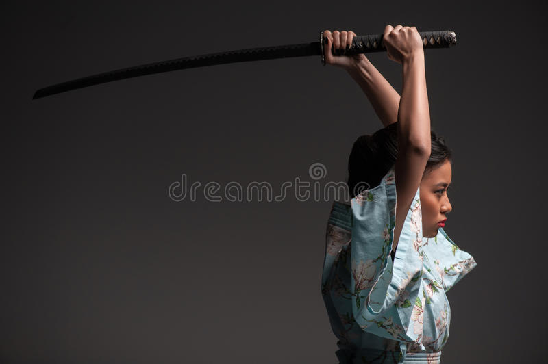 Japanese woman with katana. Aggressive move. Side view portrait of young beautiful Japanese woman in kimono attacking with katana sword while standing against royalty free stock images