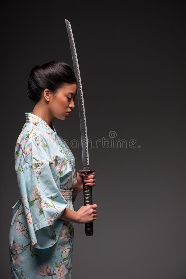 Japanese woman with katana. Total concentration. Side view portrait of young beautiful Japanese woman in kimono holding katana sword by her head while standing royalty free stock images