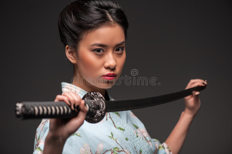 Japanese woman with katana. Total concentration. Side view portrait of young beautiful Japanese woman in kimono looking aggressively at camera and holding katana stock photo