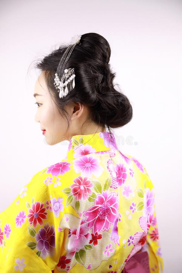 Traditional Asian Japanese beautiful Geisha woman wears kimono smile and hold a fan on hand on a white background. Japanese woman with kimono Japanese bride royalty free stock photo