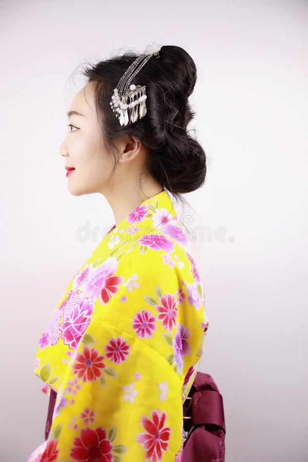 Traditional Asian Japanese beautiful Geisha woman wears kimono smile and hold a fan on hand on a white background. Japanese woman with kimono Japanese bride stock image