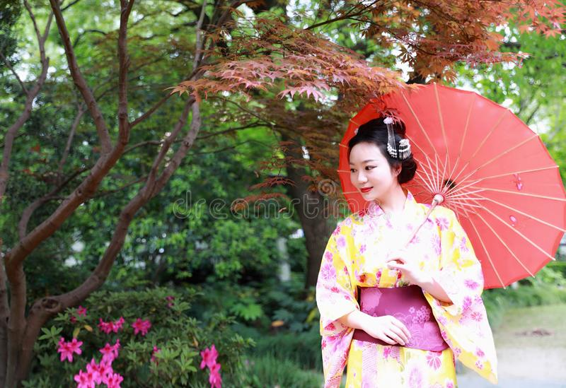 Traditional Asian Japanese beautiful Geisha woman wears kimono hold a umbrella on hand in a summer nature. Japanese woman with kimono Japanese bride smiling royalty free stock photography