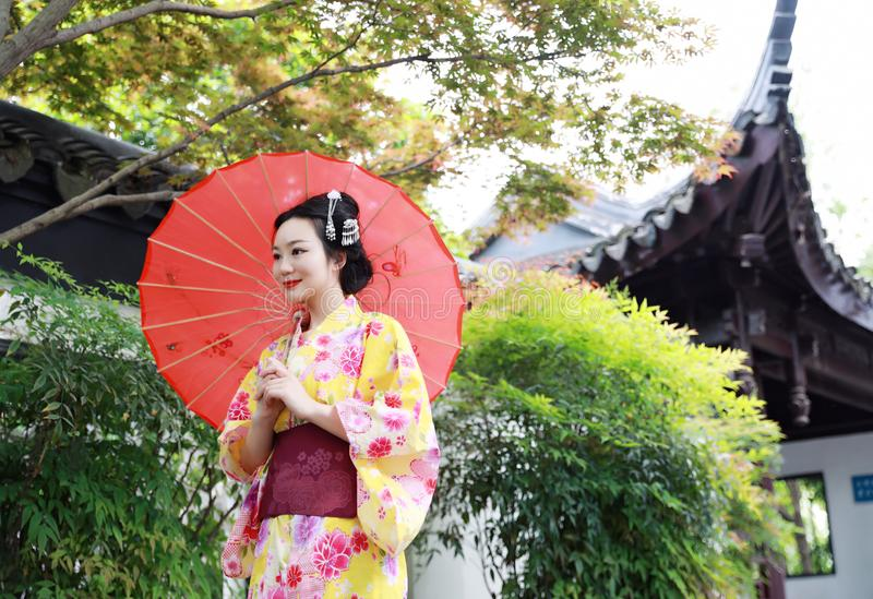 Traditional Asian Japanese beautiful woman bride wears kimono with red umbrella in front of a temple in outdoor spring garden. Japanese woman with kimono royalty free stock photography