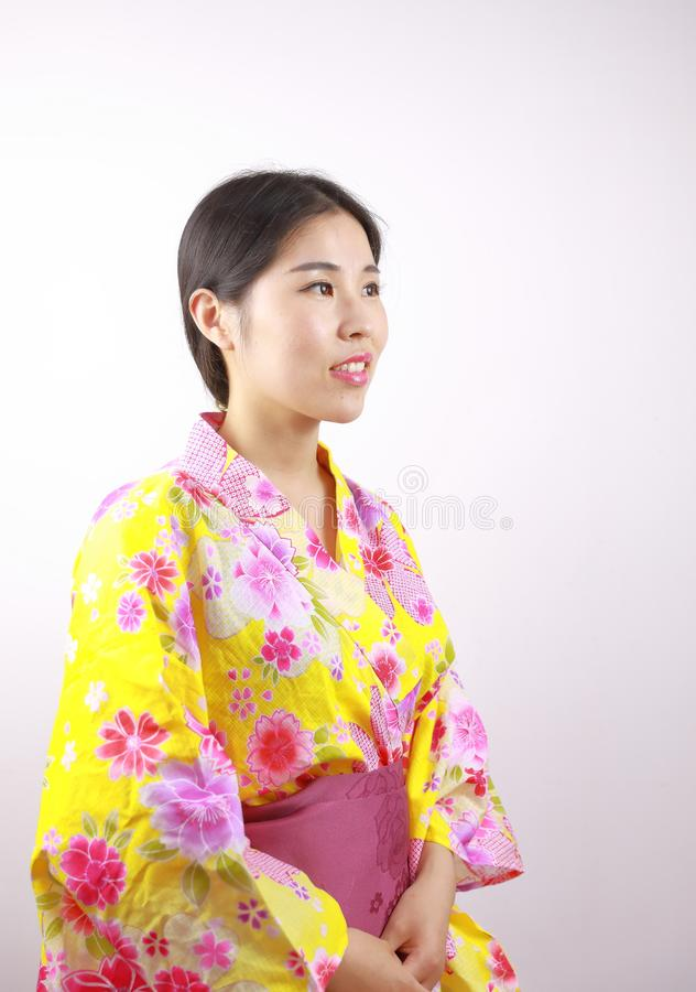 Traditional Asian Japanese beautiful geisha woman wears kimono close up blank white background. Japanese woman with kimono Japanese bride smiling stand by bamboo royalty free stock photography