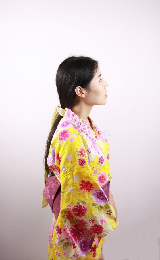 Traditional Asian Japanese beautiful geisha woman wears kimono close up blank white background. Japanese woman with kimono Japanese bride smiling stand by bamboo royalty free stock photo