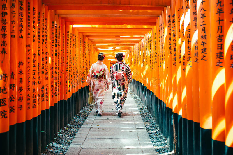 Japanese woman in kimono dress among red wooden Tori Gate at Fushimi Inari Shrine in Kyoto, Japan stock photo