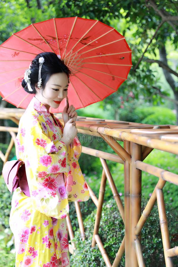 Traditional Asian Japanese beautiful Geisha woman wears kimono hold a umbrella on hand in a summer graden. Japanese woman with kimono Japanese bride smiling royalty free stock image
