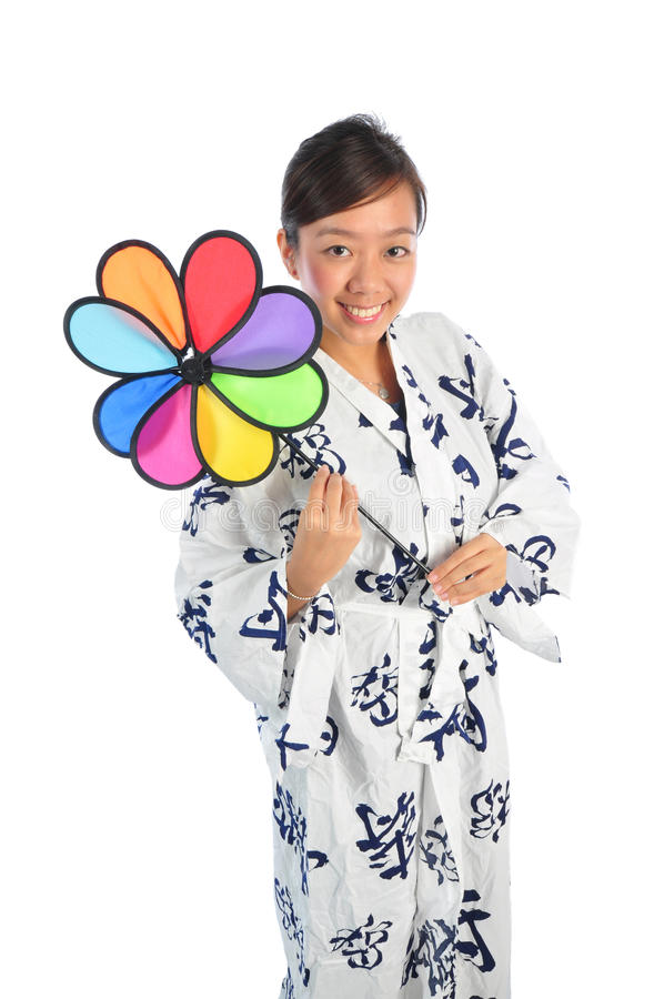 Japanese Woman playing with colorful windmill. Beautiful young Asian Woman picture taken from the top to give a big doll head effect royalty free stock image