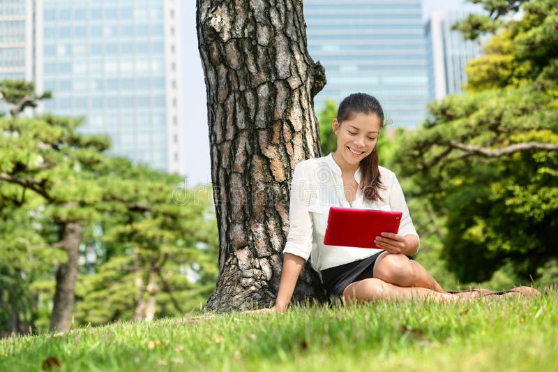 Japanese woman reading using tablet app in Tokyo. Young adult student studying e book with pc touchpad ereader computer or digital tablet in park near Ginza royalty free stock image