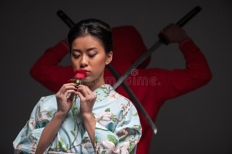 Japanese woman with rose. Oriental culture and traditions. Young beautiful Japanese woman in kimono holding a rose while standing against grey background with royalty free stock image