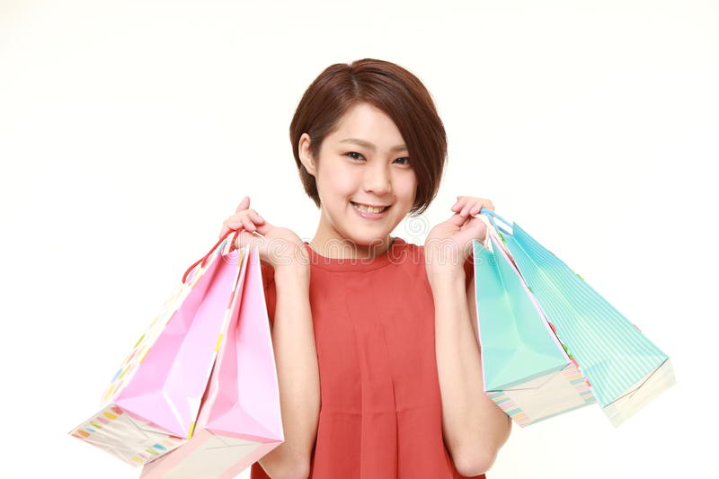 Japanese woman with shopping bags. Studio shot of young Japanese woman on white background stock images