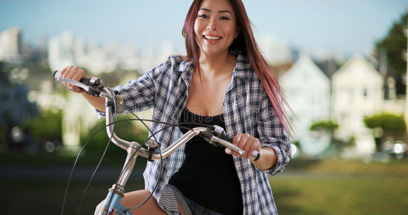 Japanese woman smiling with her bike at the park royalty free stock photos