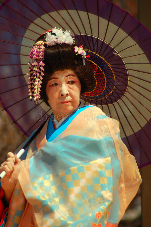 Japanese Woman in Traditional Dress. An elderly Japanese woman demonstrates the quiet grace in traditional dress royalty free stock image