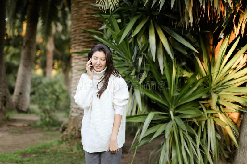 Japanese woman in tropical park talking by smartphone near palm. stock photos