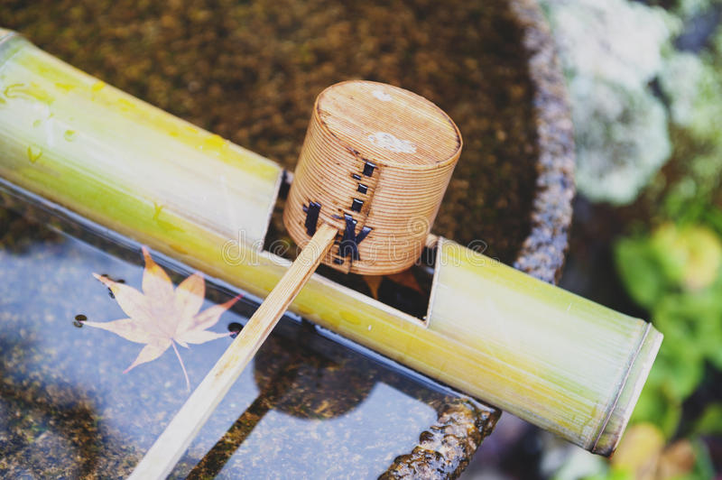 Japanese wooden purification dipper in a chozubachi or water basin used to rinse the hands in Japanese temples. Shrines, and gardens stock photography