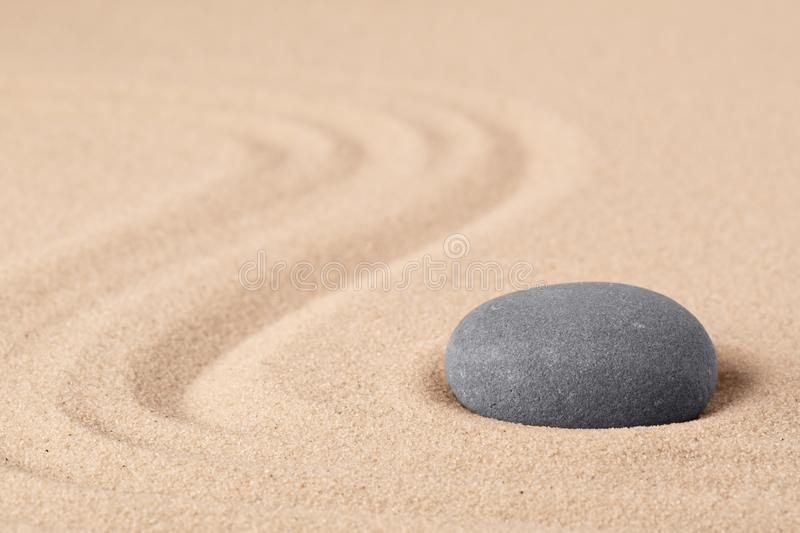 Japanese zen meditation garden with a round stone on sandy background with copy space royalty free stock photos