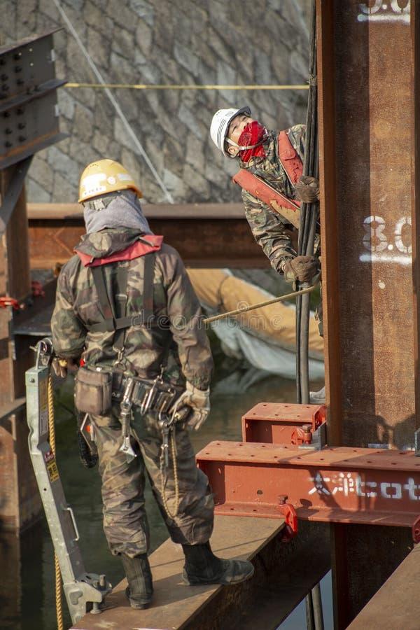 Japanische Arbeitskräfte auf einem Bohrloch lizenzfreies stockfoto
