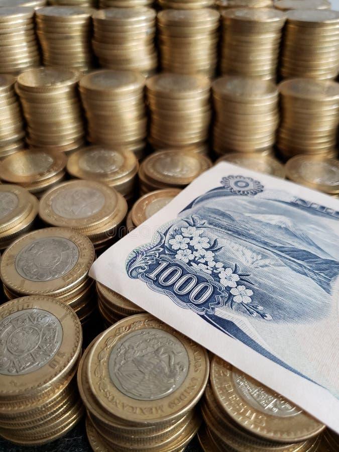 Japanische Banknote von 1000 Yen und Staplungsmünzen von zehn mexikanischen Pesos stockfotografie