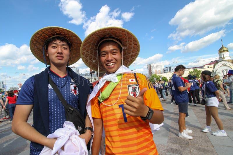 Japanische Fans des Fußballs lächelnd zwei Leute vor Fußballspiel stockfotos