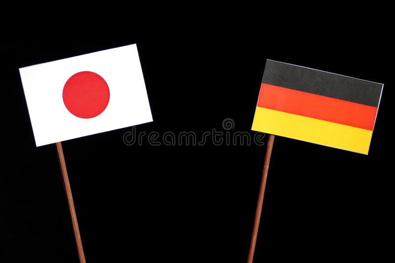 Japanische Flagge mit deutscher Flagge auf Schwarzem stockbild