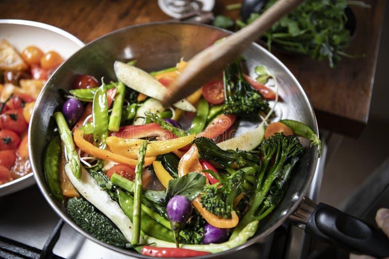 Japanische Frau, die Aufruhr gebratenes Gemüse kocht stockbild