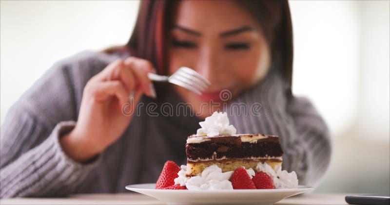 Japanische Frau, die zu Hause Kuchen isst stockbild