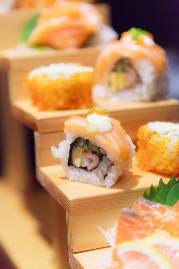 Japanische frische Fischfutter-Teller-Menü-, Salmon Sushi- und Sashimi-Zusammenstellung, die auf hölzernen Schritten auf traditio stockbild