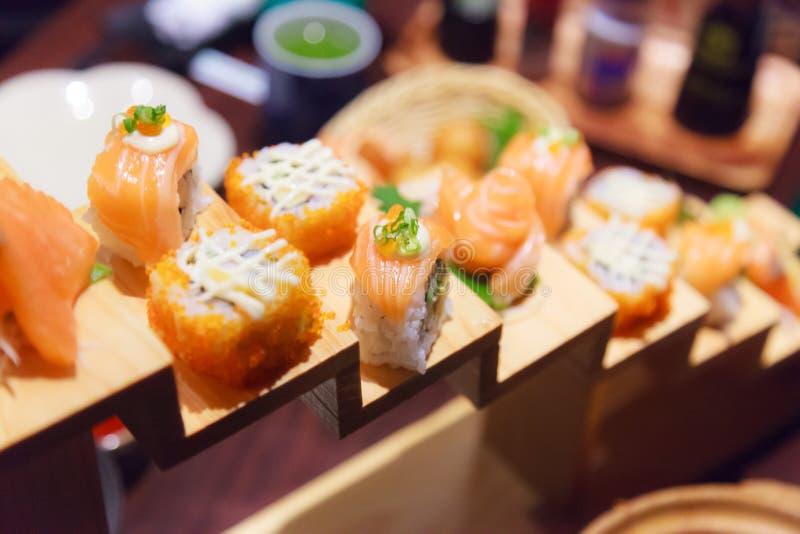 Japanische frische Fischfutter-Teller-Menü-, Salmon Sushi- und Sashimi-Zusammenstellung, die auf hölzernen Schritten auf traditio stockfoto