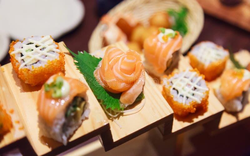 Japanische frische Fischfutter-Teller-Menü-, Salmon Sushi- und Sashimi-Zusammenstellung, die auf hölzernen Schritten auf traditio stockbilder