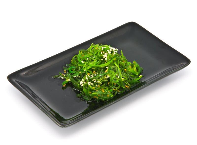 Japanische Küche, Meerespflanze-Salat in der schwarzen Platte lizenzfreie stockfotos