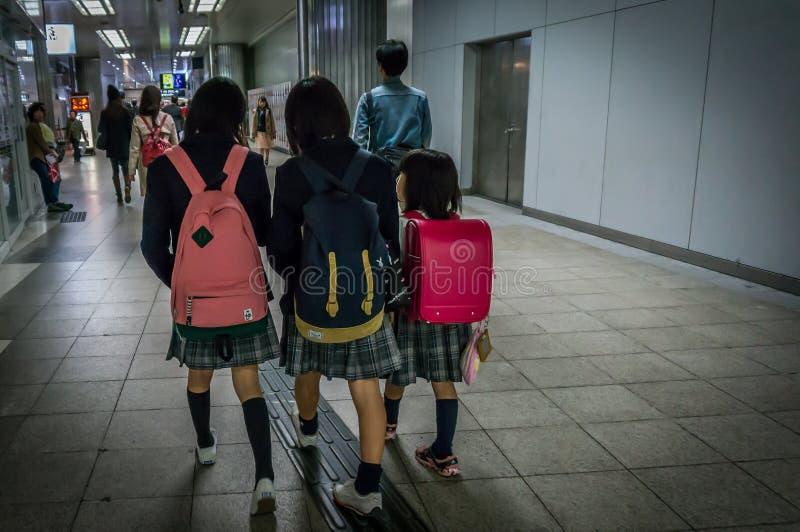 Japanische Kinder fahren zur Schule zusammen mit Schwestern mit der Metro lizenzfreies stockbild