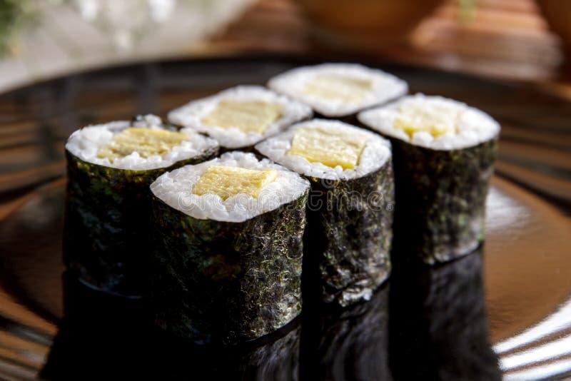 Japanische Lebensmittel tamago maki Sushi auf Schwarzblech stockfoto