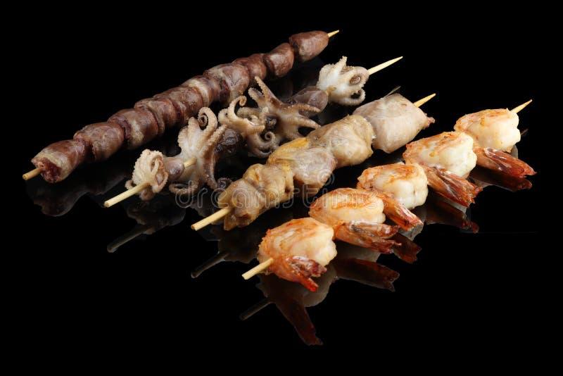 Japanische Meeresfrüchtekebabs Nahrungsmittelfoto auf schwarzem Hintergrund mit Reflexion stockfotos