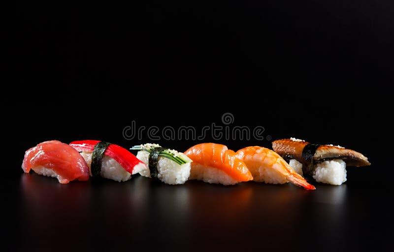 Japanische Meeresfrüchtesushi, auf schwarzem Hintergrund stockbilder